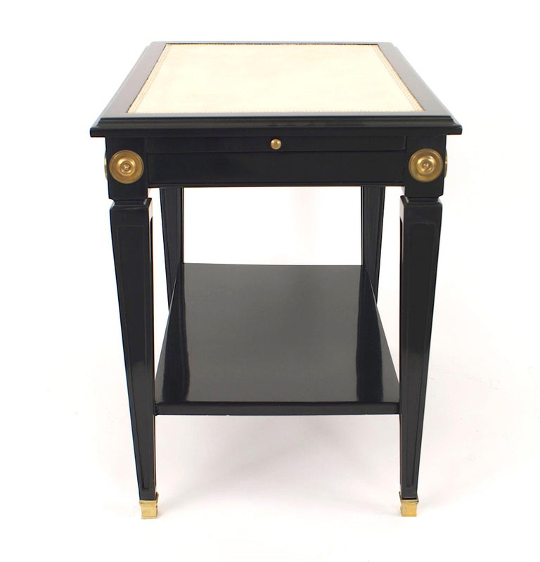 Pair of French 1940s (Louis XVI style) ebonized and bronze trimmed low end tables with a shelf and white inset leather top with a matching slide shelf on square tapered legs (stamped: JANSEN).  Maison Jansen was a Paris-based interior