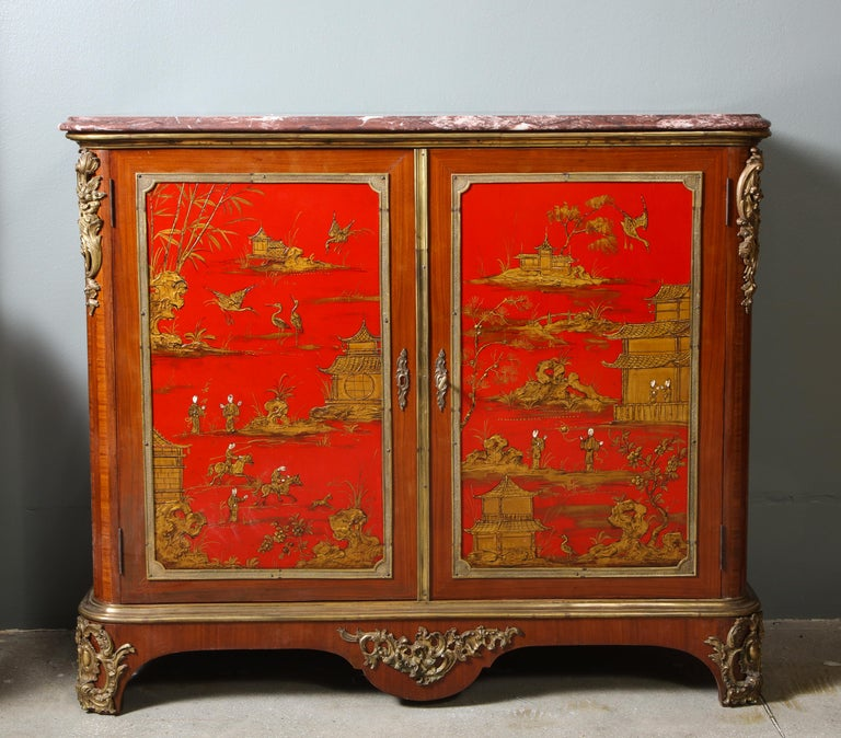 Each chinoiserie lacquered and gilt bronze mounted cabinet, attributed to Maison Jansen, with a marble top, over a pair of doors with bronze framed red lacquer panels, the sides with conforming decoration, the whole all over decorated with gilt