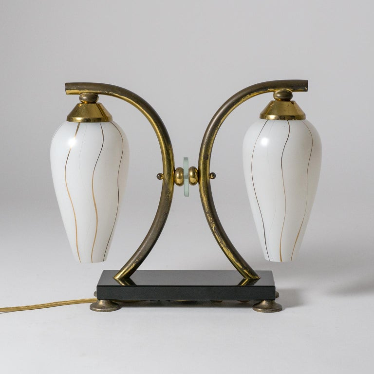 Rare pair of French midcentury table lamps with polished black stone base, brass arms and two enameled glass diffusers. The diffusers are enameled white on the outside with fine incisions and gold paint lines. Fine original condition with a fair