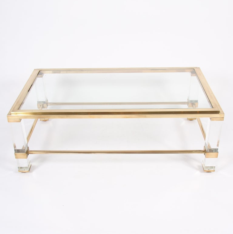 This pair of elegant brass and Lucite coffee tables date back to 1960s, France.
