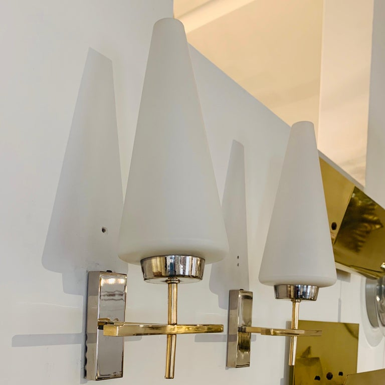 An excellent pair of 1970s French brass and polished chrome sconces with white opaline glass cone shades. Rewired.