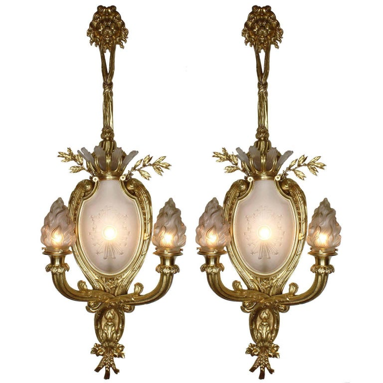A Palatial pair of French 19th-20th century Louis XV style figural gilt-bronze and frosted molded-glass two-light wall light luminéres. Each sconce centered with an ovoid frosted molded glass plaque edged with a sun-burst design below six frosted