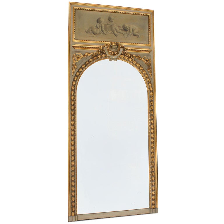 A fine pair of French 19th-20th century Louis XV style grey and parcel giltwood carved trumeau mirror frames. Each frame with an oil on canvas depicting allegorical playful putti and cherubs with a cage, one playing a horn, both within a