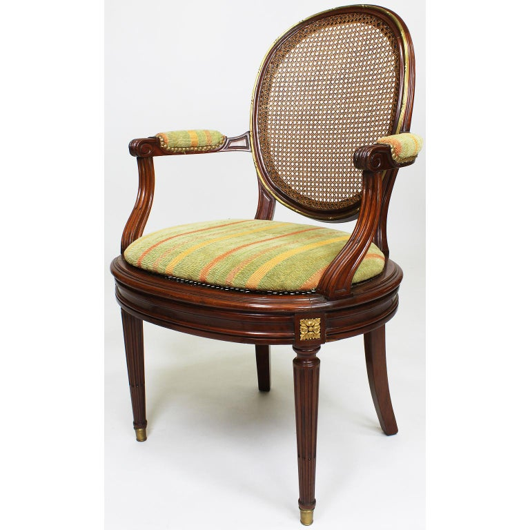 A fine pair of French 19th-20th century Louis XVI style Belle Époque mahogany and ormolu mounted dining or desk armchairs. The ovoid cane-backrests and seats, with padded open armrests, surmounted with a banded gilt-bronze trim and medallions,