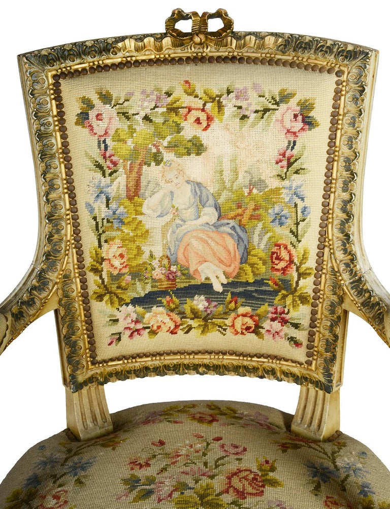 A good quality pair of late 19th century French Louis XVI style ivory and gilt decorated armchairs each with wonderful carved scrolling motif, foliate and ribbon decoration. The tapestry seat covers with brightly color scenes of lovers under a tree,