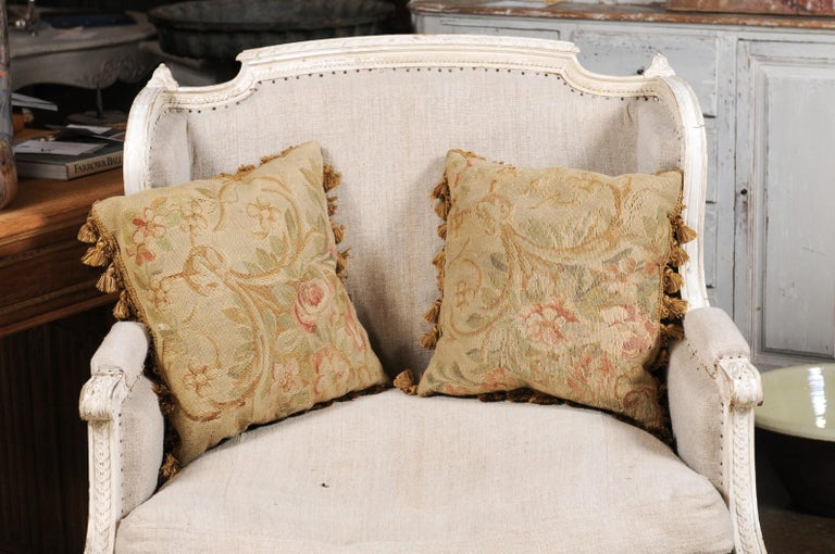 A pair of French square shaped Aubusson tapestry pillows from the 19th century, with floral decor and tassels. Created during the 19th century in the Aubusson tapestry manufacture located in central France, each of these pillows features a delicate
