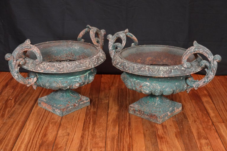 Pair of French 19th century cast iron garden urns with handles. The urns having chipping green paint that add to their beauty.