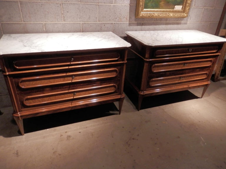 Beautiful pair of 19th century French Louis XVI walnut and fruitwood inlayed and burled commodes with the original carerra marble tops. Beautiful woods and inlay.