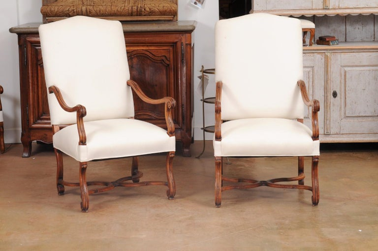 A pair of French Louis XIV style walnut armchairs from the 19th century, with scrolling arms, cross stretchers and new upholstery. Created in France during the 19th century, each of this pair of walnut armchairs features a slanted back connected to