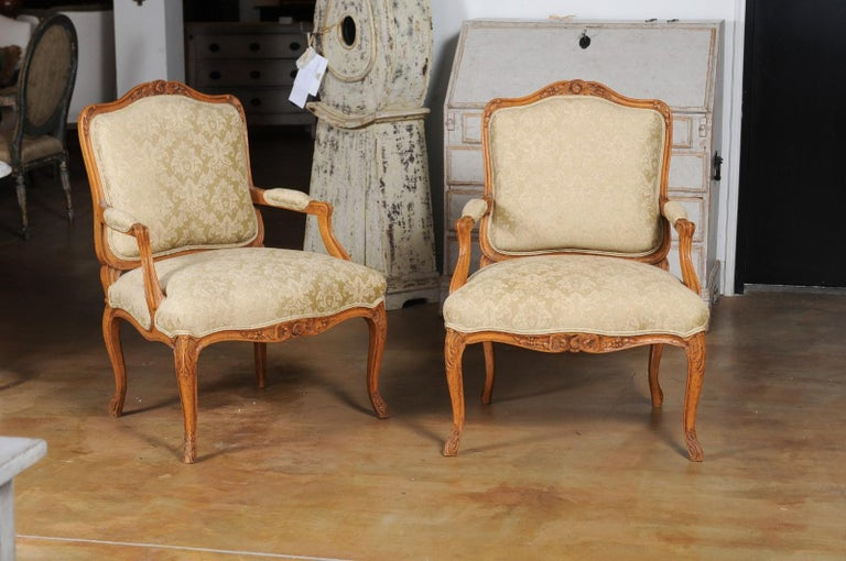 A pair of French Louis XV style in light walnut fauteuils from the 19th century, with new upholstery. Created in France during the 19th century, this pair of armchairs presents the stylistic characteristics of the Louis XV era. Each chair features a