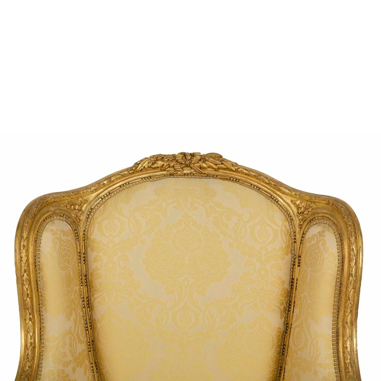 An exquisite pair of French 19th century Louis XVI st. giltwood Bergères. Each chair is raised by four circular tapered fluted legs below a richly chased giltwood laurel frieze. The scrolled giltwood arms continue at each side to the top frieze