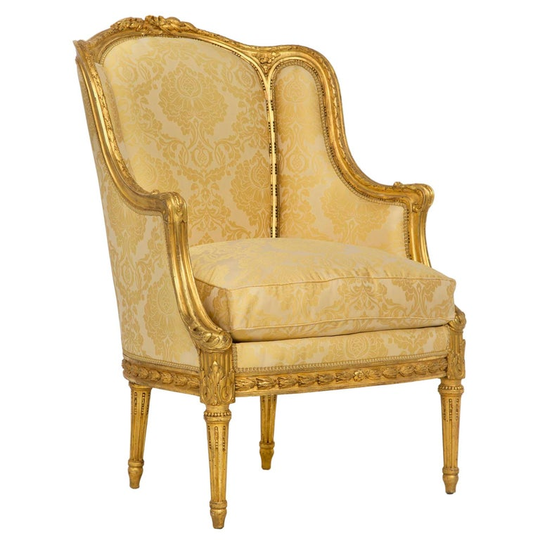 An exquisite pair of French 19th century Louis XVI St. giltwood Bergère. Each chair is raised by four circular tapered fluted legs below a richly chased giltwood laurel frieze. The scrolled giltwood arms continue at each side to the top frieze