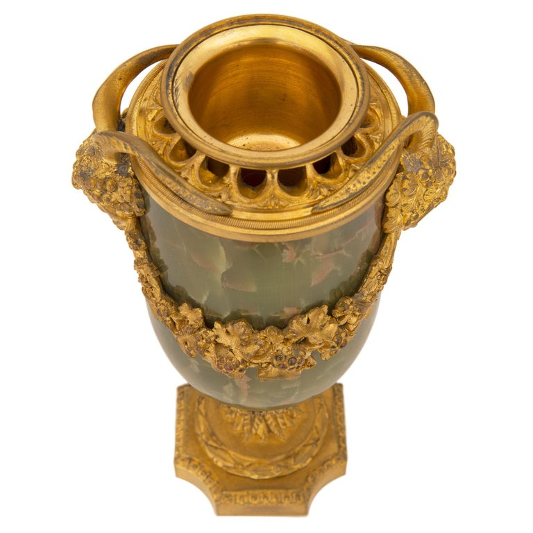 A remarkable pair of French 19th century Louis XVI st. onyx and ormolu lidded urns. Each urn is raised by a square ormolu base with concave corners and a delicate Coeur de Rai wrap around band. The socle shaped pedestals display Fine wrap around