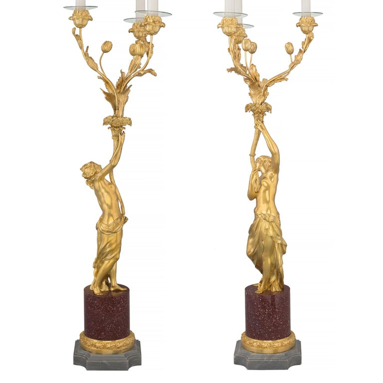 A stunning and extremely high quality true pair of French 19th century Louis XVI style ormolu, Bleu Turquin marble and Porphyry candelabras. Each candelabra is raised by by a square Bleu Turquin marble base with concave corners and an elegant and