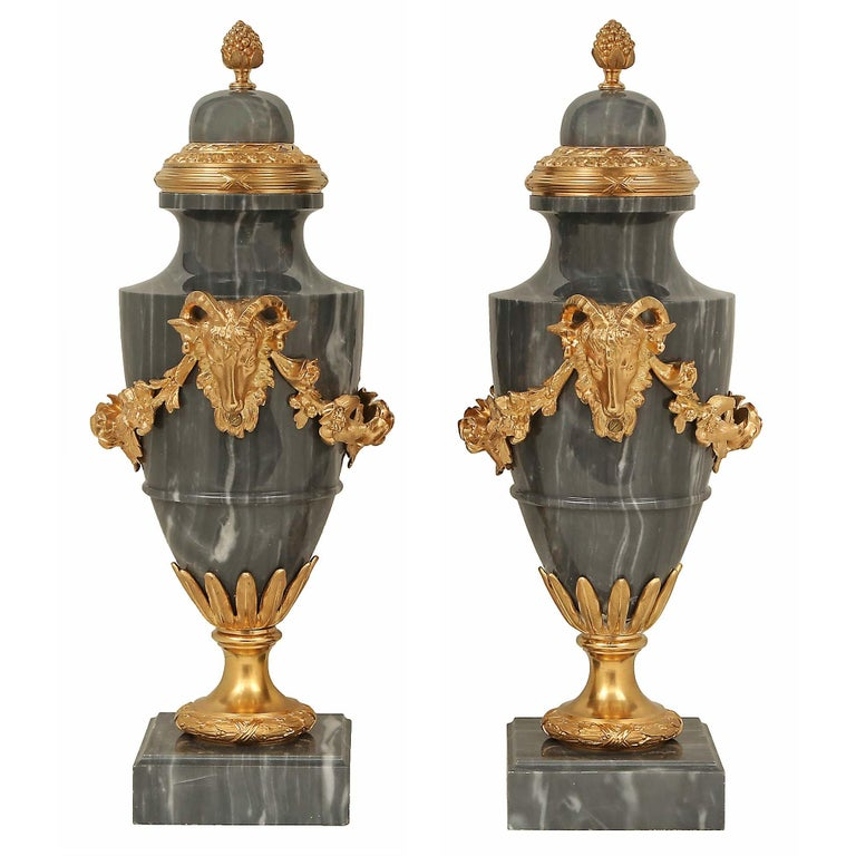A striking pair of French 19th century Louis XVI st. Blue Turquin marble and ormolu urns. Each urn is raised by a square marble base with a mottled border and an ormolu satin and burnished socle pedestal with a finely chased berried laurel band. The