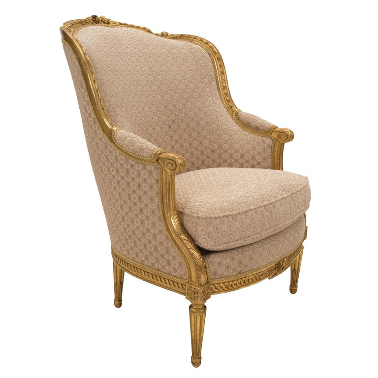 A striking pair of French 19th century Louis XVI style giltwood Bergères à Oreilles. Each armchair is raised by circular tapered fluted legs below fine block rosettes. Extending along the frieze are impressive and wonderfully carved interlocking