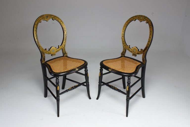 Set of two French antique chairs from the Napoleon III era in neoclassical style in ebonized mahogany and giltwood. A charming pair of side, accent or salon chairs in their original cane seats of beautiful condition and medallion shaped