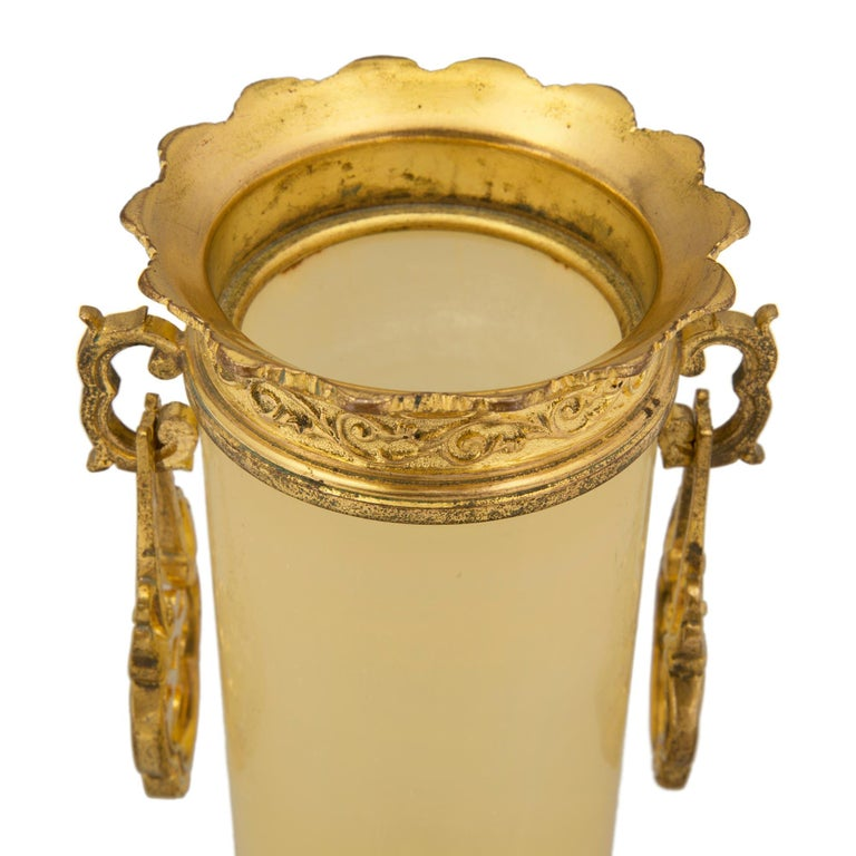 A charming and most decorative pair of French 19th century Napoleon III period Alabastro Trasparente and ormolu vases. Each beautiful vase is raised by three scrolled foliate feet. Above the feet are lovely pierced wrap around ormolu bases with fine