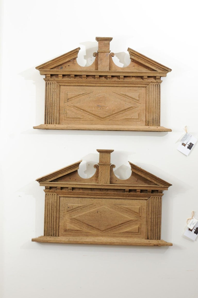 A pair of French over door panels from the 19th century, with broken pediments, pilasters and fluted motifs. Created in France during the 19th century, each of this pair of over doors captures our attention with its broken pediment marked with a
