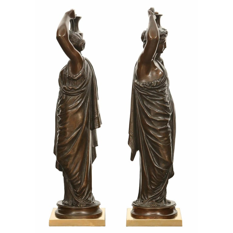 A charming true pair of French 19th century patinated bronze statues signed H. Ferrat. Each bronze is raised by a square ormolu base and with a circular patinated bronze pedestal. The bronzes depict female maidens draped in classical attire carrying