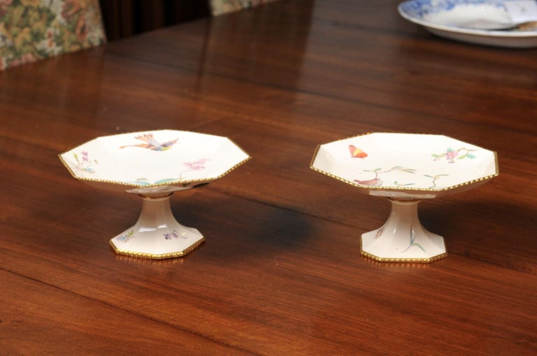 A pair of French porcelain compotes from the 19th century, with painted birds, flowers and gold trim. Born in France during the dynamic 19th century, each of this pair of compotes features an octagonal top, adorned with painted birds, butterflies,