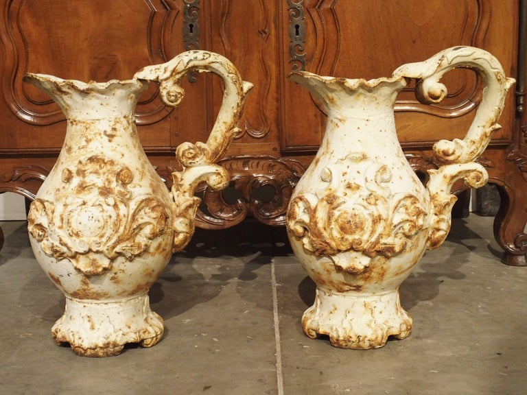 This pair of large antique French parcel paint pitchers has very ornate designs. In the Rococo style, their motifs are drawn from nature. Their scalloped upper rim imitates the shell motif and their handles are acanthus leaf C-scrolls. The shaped