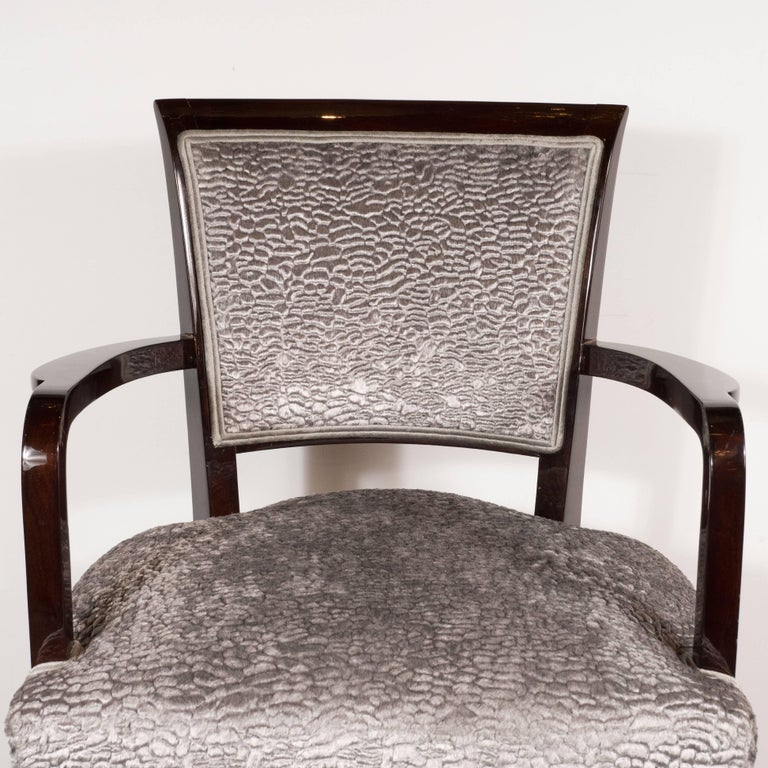 This stunning pair of armchairs were realized by the celebrated French designer Jules Leleu, circa 1930. They feature hourglass shaped rectangular backs; tapered rectangular legs with nickelled sabots; and streamlined arms realized in mahogany. They
