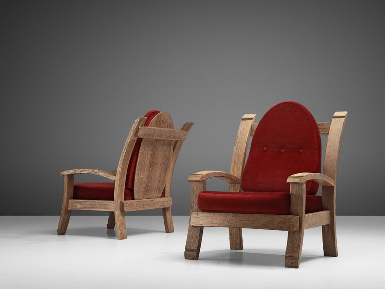 Pair of lounge chairs, oak and fabric, France, 1940s  Charming French Art Deco armchairs made of oak. The design features bulky forms with elements of a throne, such as the high, almost majestic backrests that slightly leans backwards. The arms