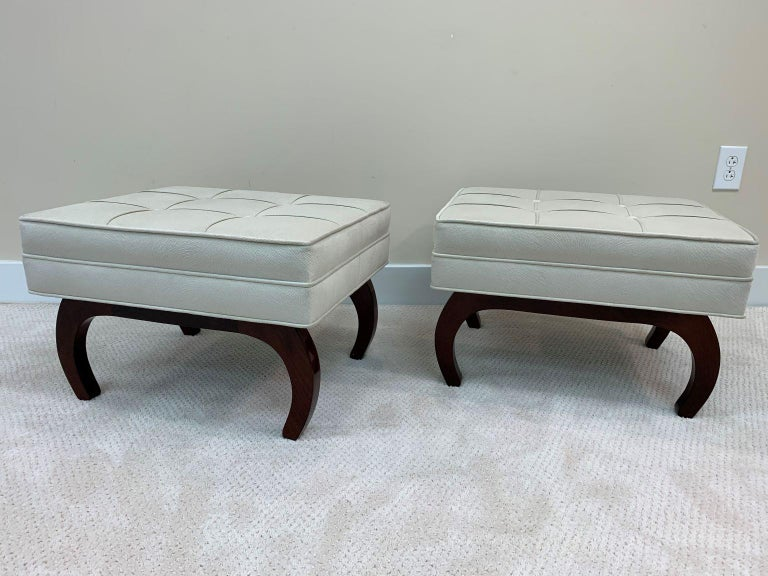 Pair of French Art Deco benches with solid walnut bases. A tailored and tufted look make these benches a perfect fit for any seating purpose. The faux pony skin upholstery is a nice compliment to the curved-leg walnut bases. Measures: Width 22.5,