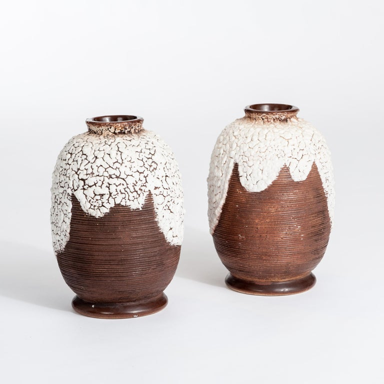 Pair of French Art Deco ceramic vases brown-offhwite signed by Louis Auguste Dage. The dark brown surface has a fine ribbed structure, the upper part displays an owwhite colored ceramic