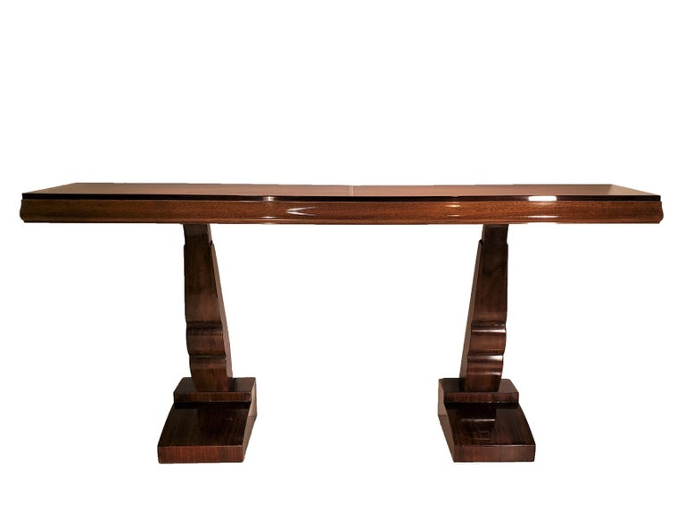 A pair of elegant, original French Modern parquetry inlaid multi wood consoles in in figured rosewood, walnut, and palisander, featuring double sculptural legs raised on stepped and flanged pediment bases. Paquebot style in a semi gloss lacquer