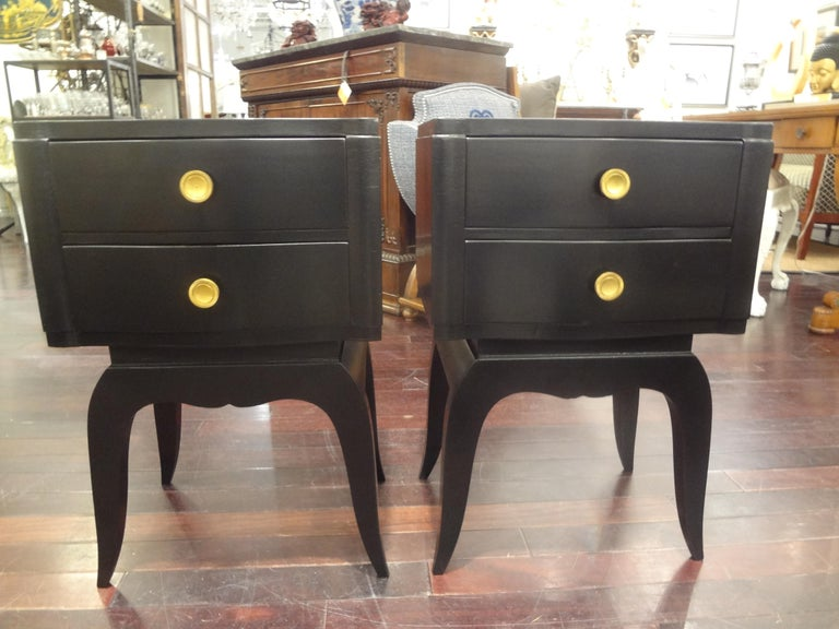 Stunning pair of French Art Deco ebonized commodes, chests, nightstands or side tables with two drawers and bronze hardware. This versatile pair of Jules Leleu inspired tables would work well in a variety of interiors and rooms and date to the 1930s.