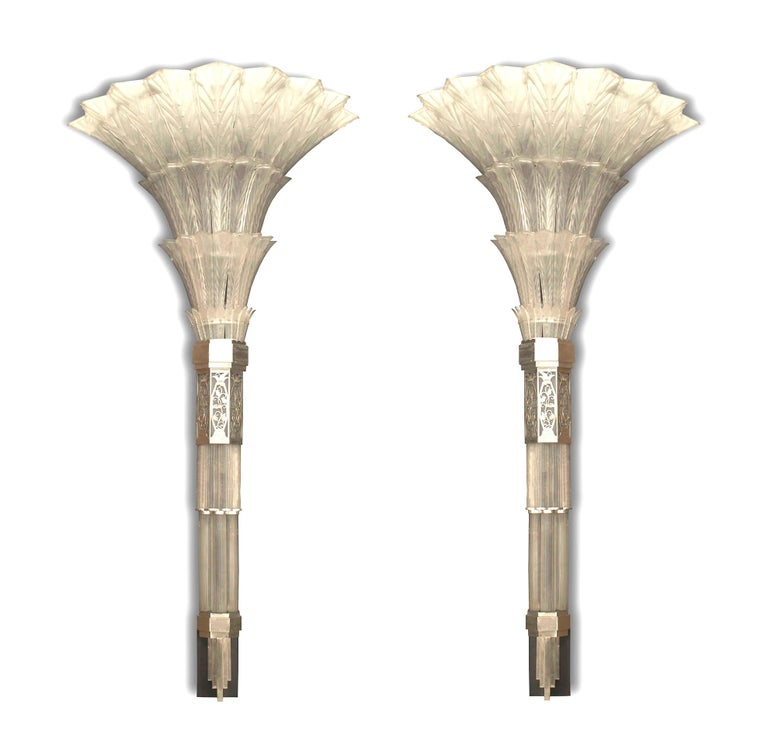 Designed by Sabino, this striking pair of 1930s French glass wall sconces features a geometric stave accented with a bottom finial beneath a band of chrome plated filigree trim joining the base to a flared and tiered foliate lamp reminiscent of the