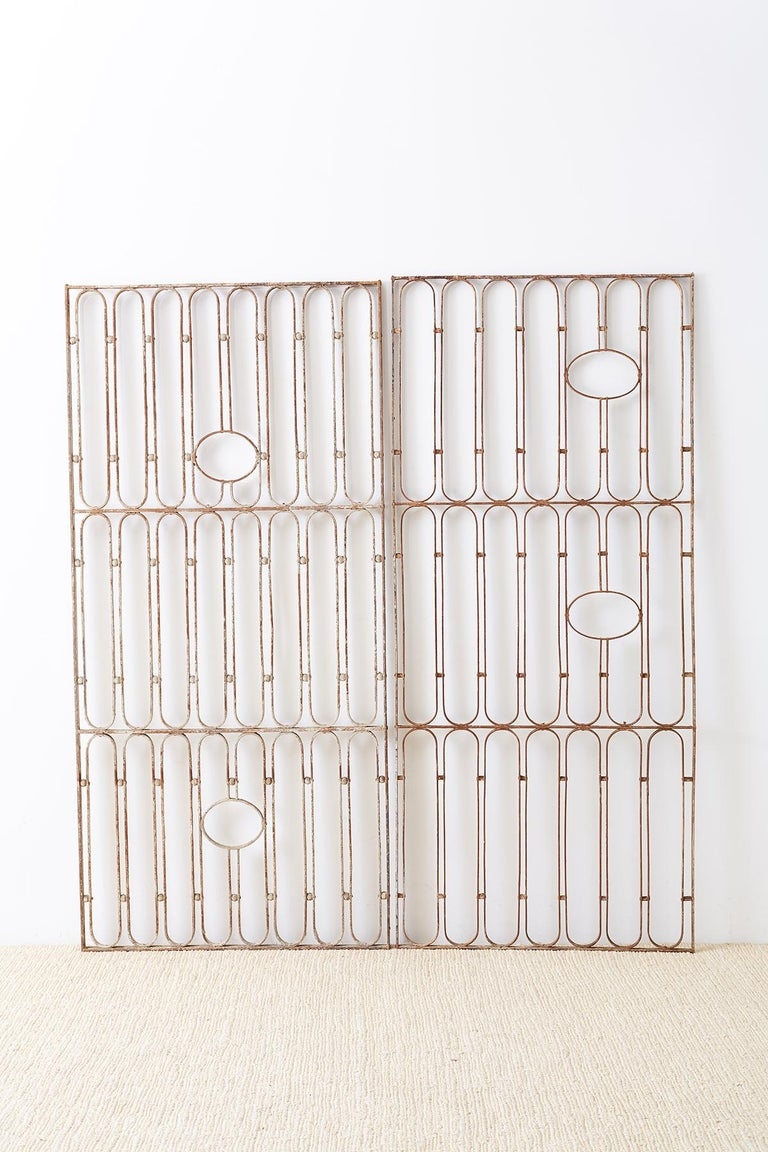 Modern pair of French art deco period garden doors, gates or grills. Features a repeating geometric pattern of long oval shapes separated by small round orbs. The patterns are broken up by pairs of round openings on each door. One door is slightly