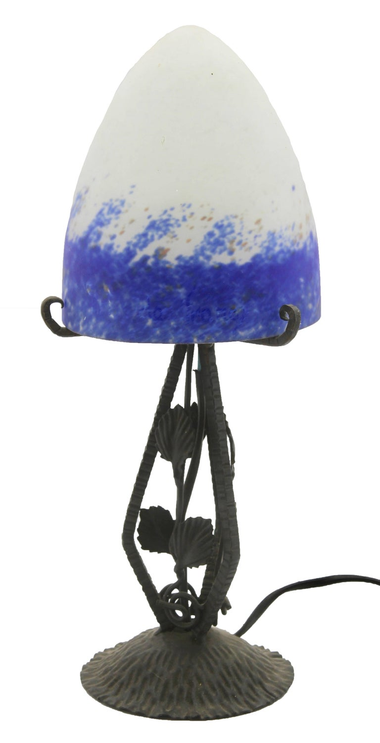 A wonderful pair of French Art Deco lamps. The stands are handmade in wrought iron with black finish patina and hammered with floral pattern. The metalwork is of excellent quality. They are crowned with bright colored shades in mottled glass paste