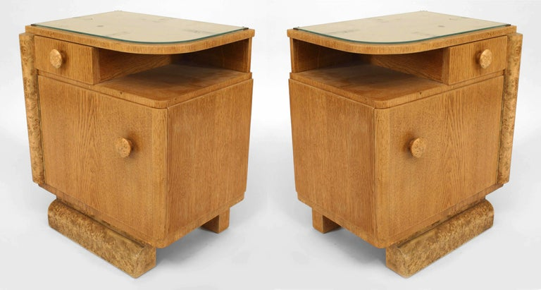 Pair of French Art Deco oak and burl wood trim bedside commodes each with a glass top above a small shelf and drawer and a larger cabinet and door.