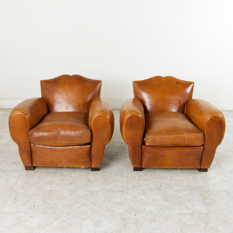This pair of mid-20th century French Art Deco period moustache back club chairs are in wonderful condition. Originally in the entryway of an elderly couple's home in France, these chairs have rarely been sat in. With a design created during the Art