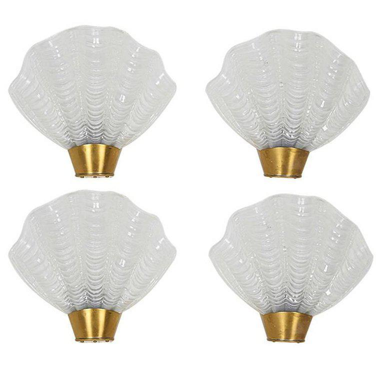 Art Deco sconces with elegant shell design. The sconces are comprised of white hand molded frosted glass with fluted details and stylized ridges created in the form of sea shells. The sconces feature petite brushed brass metal fittings and frames.