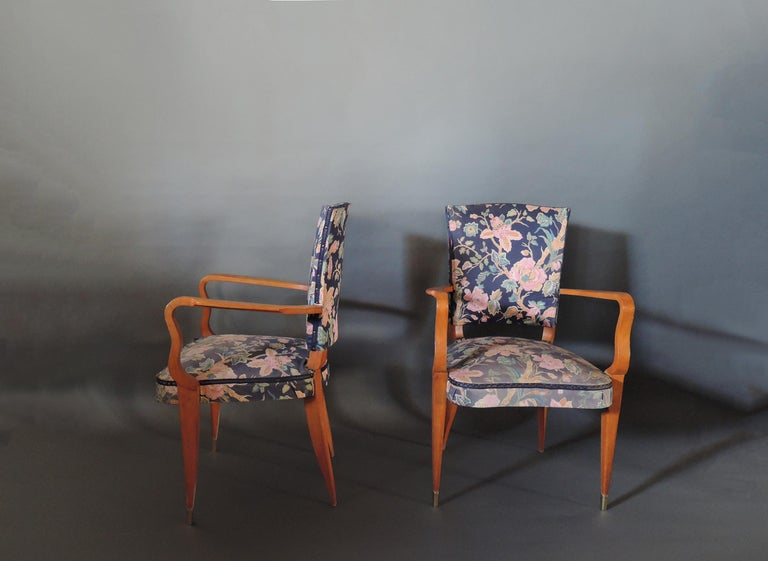 A pair of French Art Deco orange stained beech armchairs with brass sabots.
