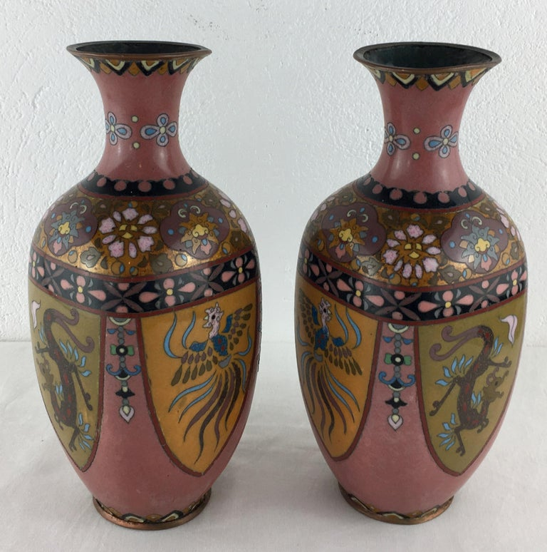 Vibrantly colored and intricately detailed pair of French Art Deco cloisonné vases with floral, geometric and animal patterns (resembles a phoenix).  Measures: 9 1/4
