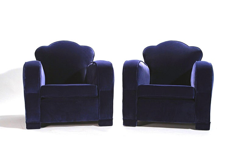 This pair of armchairs embodies the smooth lines of the Art Deco club chairs that came on the market shortly after the First World War. They're attributed to designer Jules Leleu. New upholstery in a deep blue velvet enhances the pair's original,