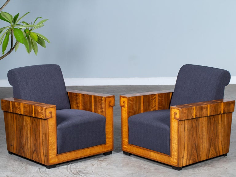 A pair of striking vintage French Art Deco walnut armchairs from France, circa 1930. The architectural aspects of the French Art Deco period are on full display here in this pair of Art Deco chairs with their geometric profile. The designer