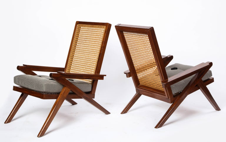 A pair of French 'Art Moderne' mahogany and caned armchairs from the 20th century. These chairs feature a rich mahogany structure, paired with a subtly caned seat and backrest to provide an elegant accent to a sitting room or front foyer. Custom