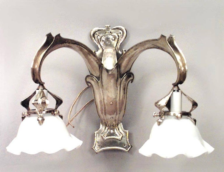 Pair of French Art Nouveau brass two-arm wall sconces with fleur de lis front panel and white scalloped glass shades.