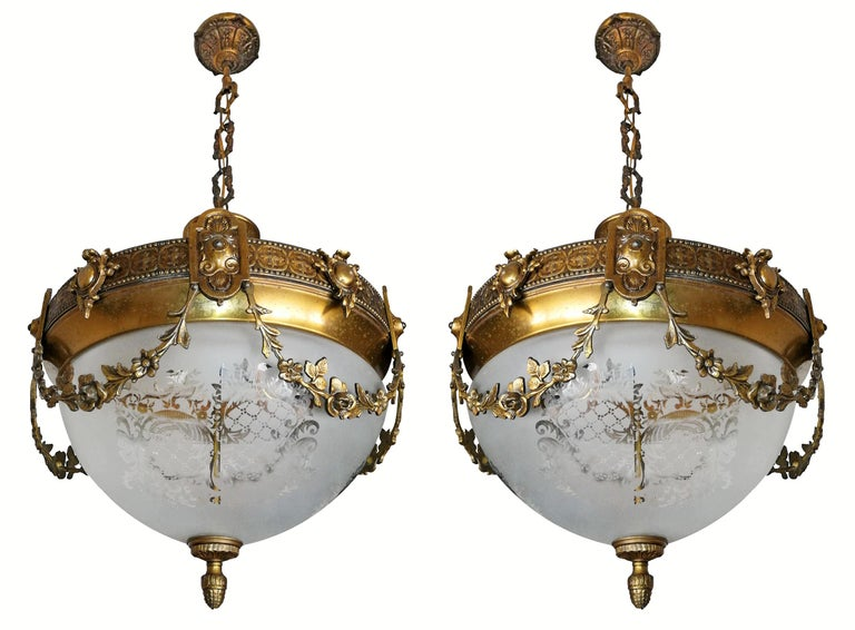 A wonderful pair of gilt bronze and etched-glass two-light ceiling fixtures decorated with fine ornaments and garlands, France, early 20th century.
