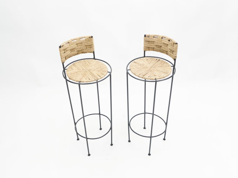 Beautiful patina is evident along the abaca rope seating and backrest of this pair of bar stools by Adrien Audoux et Frida Minet, giving away their vintage status. This natural style is typical of the French design of Audoux-Minet. Timeless