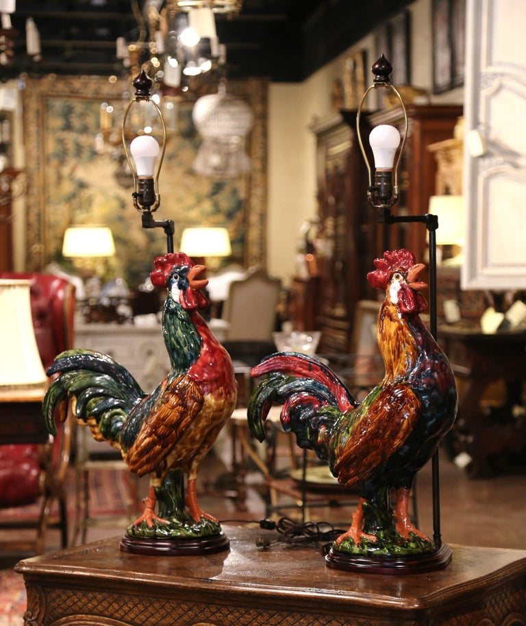 Bring a little country French flair into your home with this colorful pair of lamps. Crafted in Normandy, France, the Majolica roosters are hand painted and have been made into large table lamps. Each fixture stands on a wooden base, has new wiring
