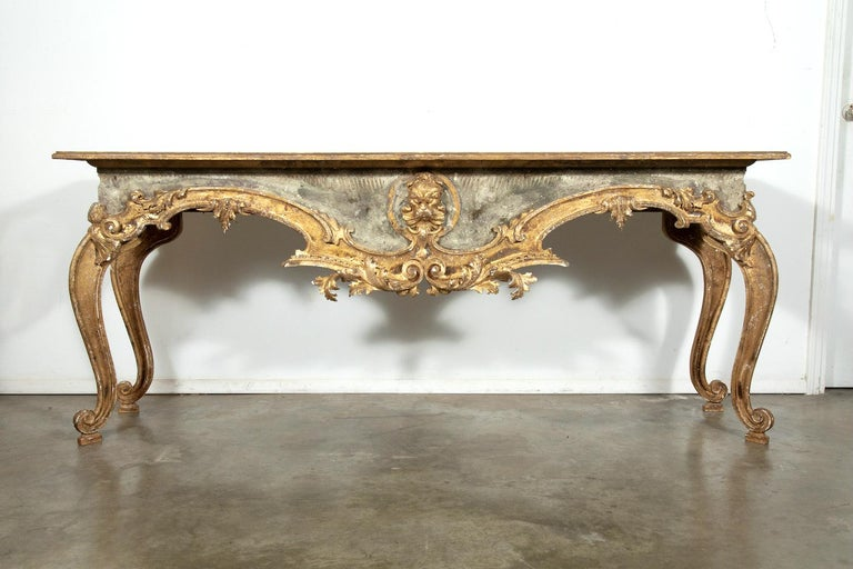 A pair of exceptional French Baroque style console tables, handmade from 18th century painted and parcel-gilt fragments, having rectangular scrubbed pine plank top. In typical Baroque manner, the ornate bases feature a central grotesque mask with