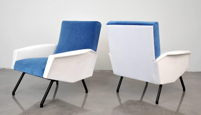 A striking pair of Mid-Century Modern club chairs with black lacquered iron legs, made in France in the 1950s. The armchairs have been recovered in an azure sky or light sapphire blue and white velvet. They are very comfortable, as the overall