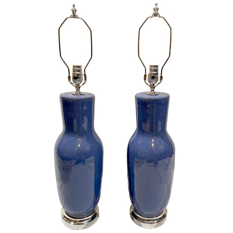 A pair of French circa 1940s blue porcelain table lamps with silvered bases. 
